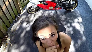 A skinny ebony girl is getting naked outside next to a bike