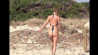 hot blonde in open sling bikini on the beach