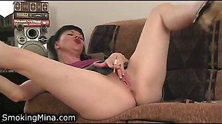 A mature lady named Mina pleasures her cunt while smoking a