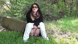 Slutty brunette in sunglasses enjoys pissing on the grass