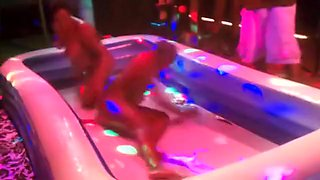 Women stripping one another oil wrestling