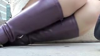 Girl in high heeled boots is exposing white thong upskirt