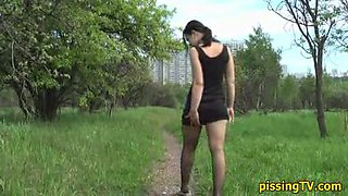 Ass view of a pissing girl in the park