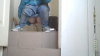 White chick in blue jeans and coat pisses in the toilet