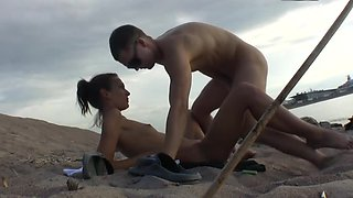 A couple is having sex on the beach together in the sun