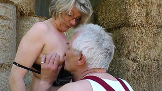 Mature lusty grey haired village slut wanks and sucks dick on straw in shed